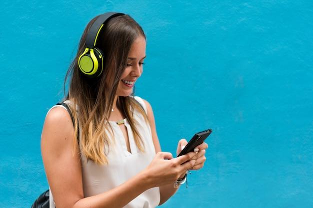 La giovane donna sta ascoltando musica con le sue cuffie su fondo blu Foto Premium