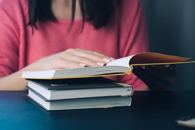 La giovane donna sta leggendo un libro a casa. sfondo sfocato orizzontale, effetto film. Foto Premium