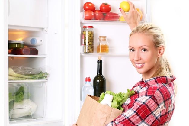 La giovane donna sta mettendo un alimento nel frigorifero Foto Gratuite