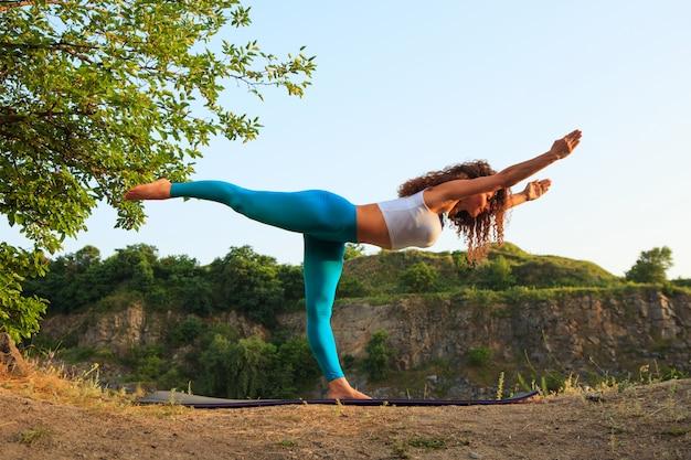 La giovane donna sta praticando yoga vicino al fiume Foto Gratuite