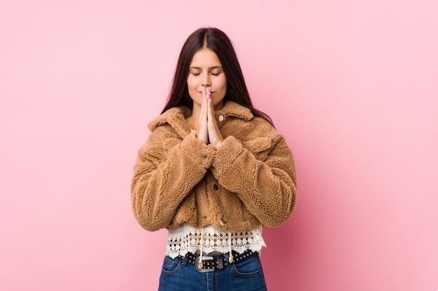 La giovane donna sveglia che si tiene per mano dentro prega vicino alla bocca, si sente sicura Foto Premium