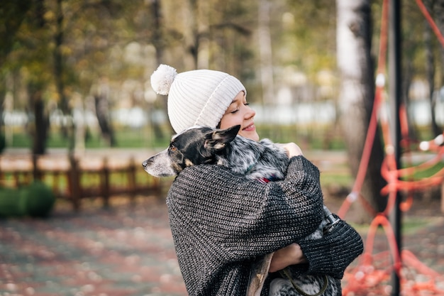 La giovane donna tiene in braccio un cane Foto Gratuite