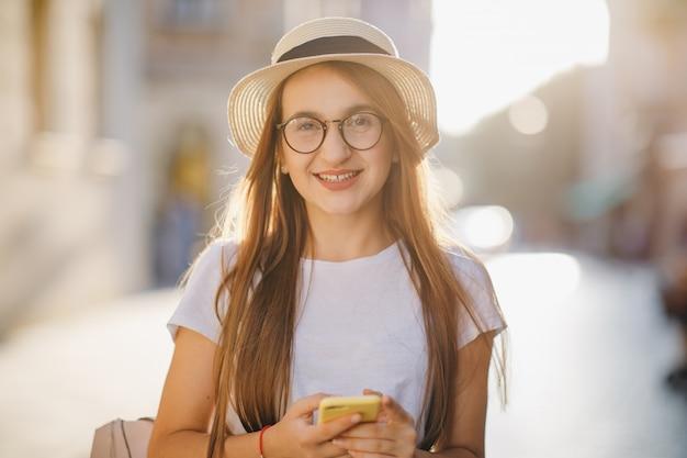 La giovane donna viaggia in cappello e occhiali si trova sulla strada della città e sms sms sul suo telefono cellulare. Foto Premium