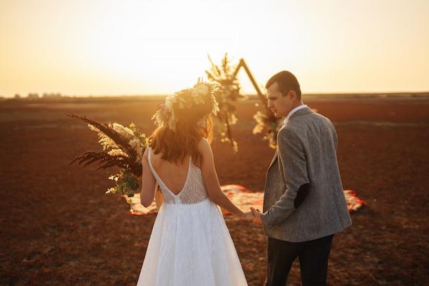 La giovane e bella sposa e lo sposo si divertono. giorno del matrimonio in stile boho. Foto Premium