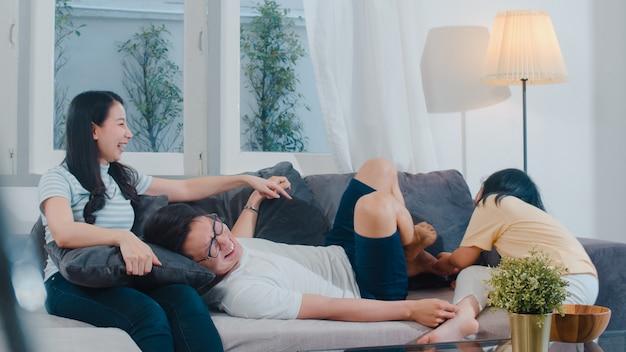 La giovane famiglia asiatica felice gioca insieme sullo strato a casa. godere cinese felice della figlia del padre e del bambino della madre che trascorre insieme il tempo in salone moderno nella sera. Foto Gratuite