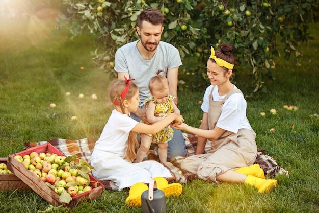 La giovane famiglia felice durante la raccolta delle mele in un giardino all'aperto Foto Gratuite
