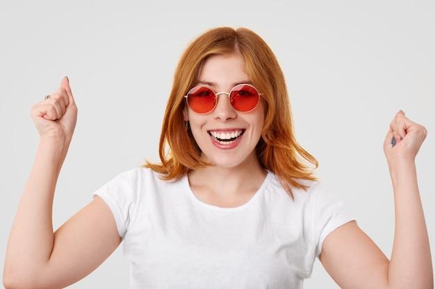 La giovane femmina felice dello zenzero di successo tiene sollevati i pugni, ha un sorriso a trentadue denti, celebra la giornata di successo Foto Gratuite