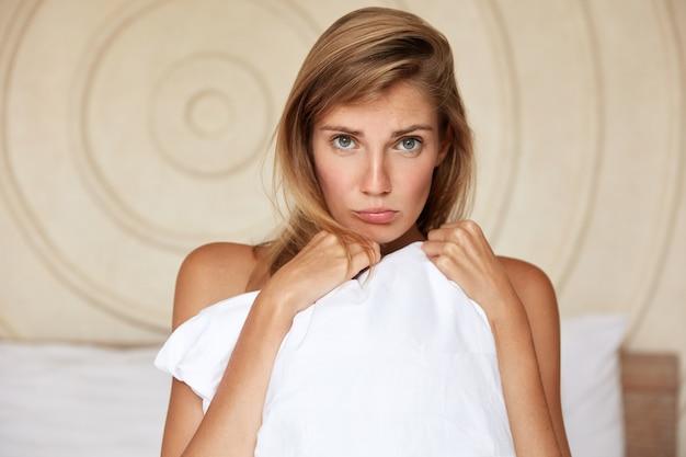 La giovane femmina infelice si sente abusata dopo aver litigato con il marito, fa il broncio e nasconde il corpo con un cuscino bianco, ha un'espressione dispiaciuta e un aspetto piacevole e attraente. la donna posa in camera da letto Foto Gratuite
