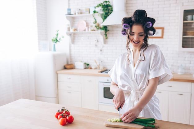 La giovane governante femminile sta allo scrittorio in cucina e taglia la cipolla verde. lavora con attenzione. tagliare il peperoncino sul lato sinistro. solo in cucina. lavorare a casa. sugar daddy paga per tutto. Foto Premium
