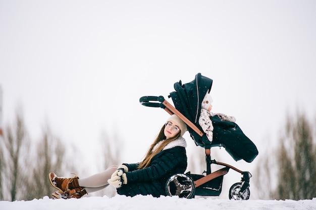 La giovane madre alla moda alla moda riposa con sua figlia che si siede in passeggiatore in parco all'aperto all'inverno. Foto Premium