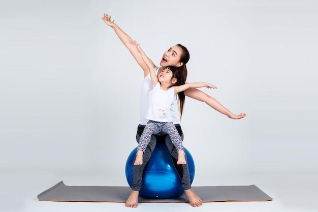 La giovane madre con la piccola figlia si esercita sulla palla di forma fisica Foto Gratuite