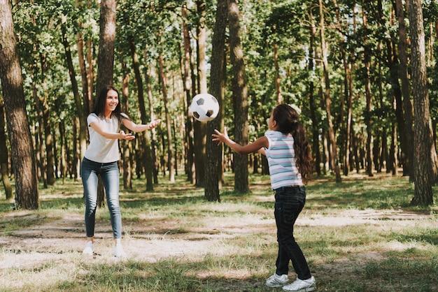 La giovane madre sta gettando la palla con una figlia. Foto Premium
