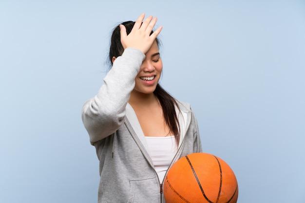 La giovane ragazza asiatica che gioca a pallacanestro sopra la parete isolata ha realizzato qualcosa e intendendo la soluzione Foto Premium