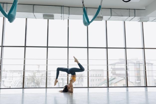 La giovane ragazza attraente che fa la forma fisica si esercita con yoga sul pavimento. finestre panoramiche Foto Premium