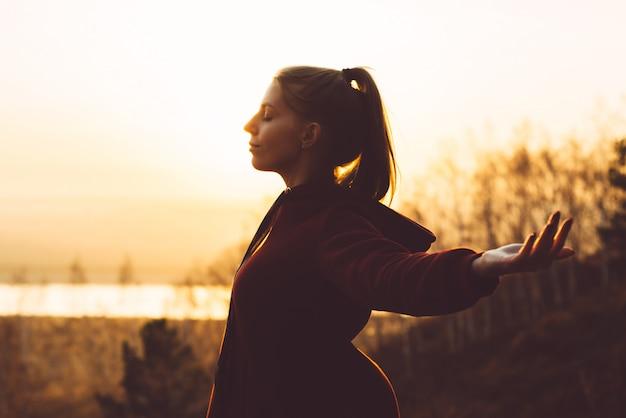 La giovane ragazza attraente in natura durante il tramonto gode dell'aria fresca Foto Premium