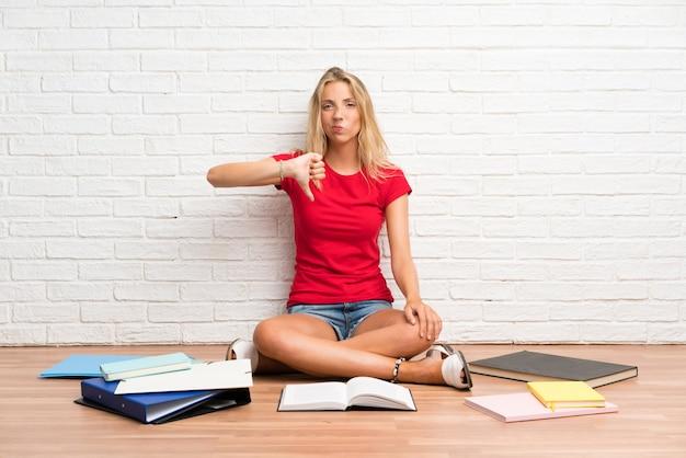 La giovane ragazza bionda dello studente con molti libri sul pavimento che mostra il pollice giù firma Foto Premium