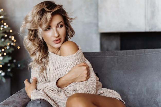 La giovane ragazza bionda sexy del primo piano si siede su un sofà in un maglione Foto Premium