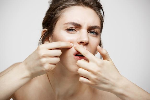 La giovane ragazza castana ha dispiaciuto della sua pelle del fronte dell'acne di problema sopra fondo bianco. cosmetologia della salute e cura della pelle. Foto Gratuite