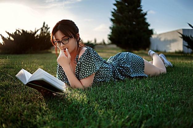 La giovane ragazza caucasica in retro vestito d'annata legge un libro sul prato inglese durante il tramonto Foto Premium