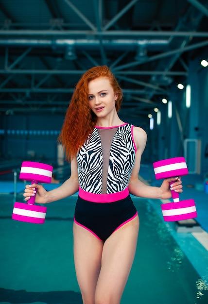 La giovane ragazza dai capelli rossi sta con la piscina delle teste di legno Foto Premium