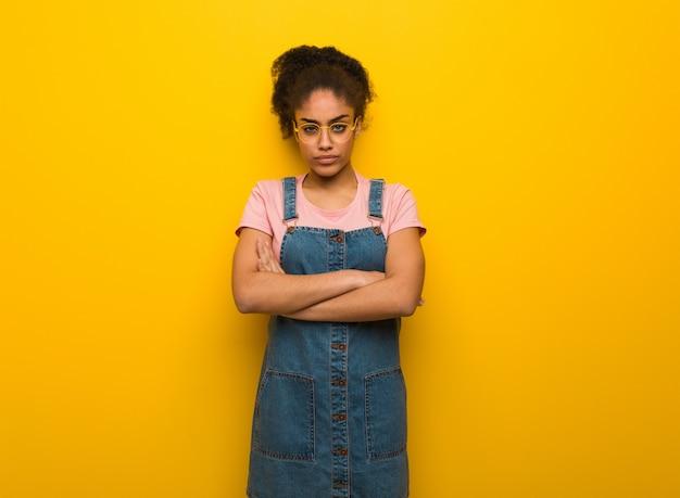 La giovane ragazza dell'afroamericano nero con l'incrocio degli occhi azzurri arma rilassato Foto Premium