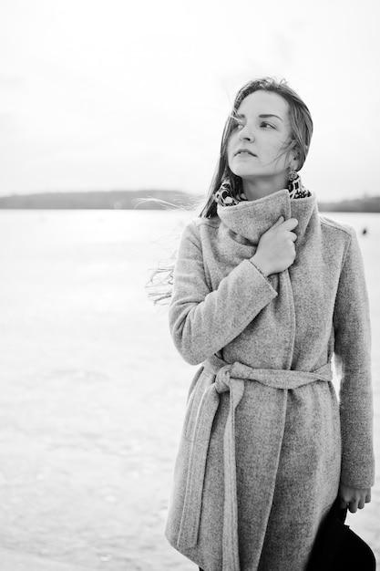 La giovane ragazza di modello in cappotto grigio e black hat ha posato contro il lago freeze. foto in bianco e nero. Foto Premium