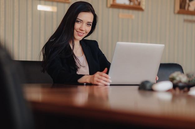 La giovane ragazza emozionale attraente in vestiti di stile di affari si siede ad uno scrittorio su un computer portatile e su un telefono nell'ufficio o nella sala Foto Gratuite