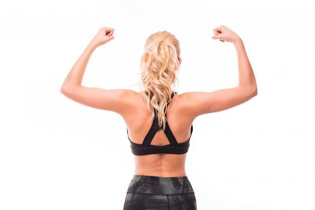 La giovane signora bionda nella cima nera dimostra i suoi muscoli dalla parte posteriore isolata su bianco Foto Gratuite