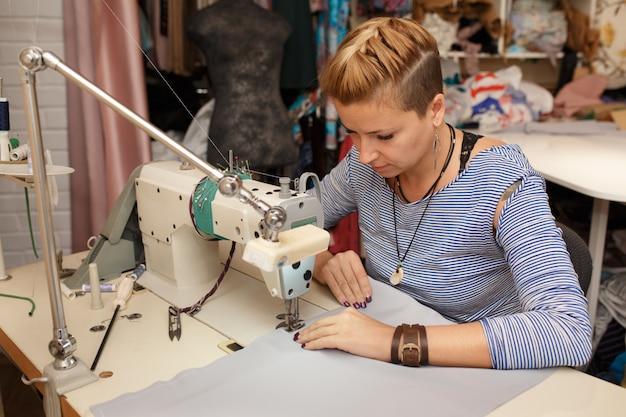 La giovane stilista bionda femminile del panno del sarto da donna lavora alla macchina per cucire Foto Premium