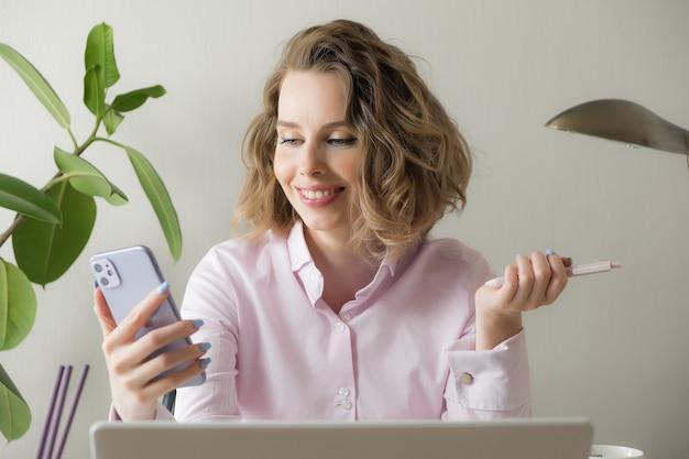 La giovane videoconferenza sorridente della donna di affari che rivolge allo smart phone parla dalla webcam nella chiacchierata online, nel servizio di assistenza clienti e nel concetto d'istruzione online di distanza. lavoro a distanza Foto Premium