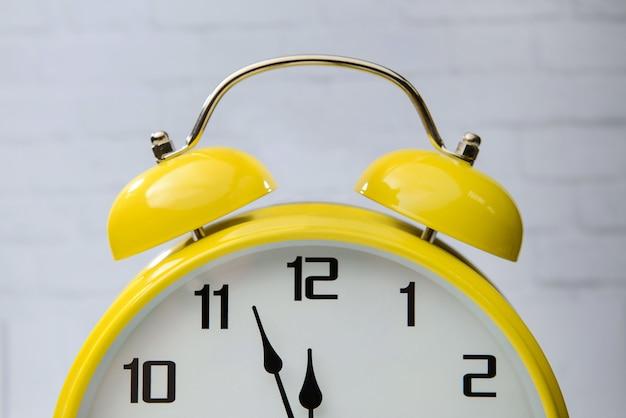 La grande sveglia gialla con le frecce si chiude su. Foto Premium