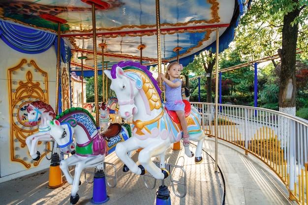 La guida della ragazza sul cavallo della zona fieristica sul giro di divertimenti del carosello al parco delle fiere all'aperto Foto Premium