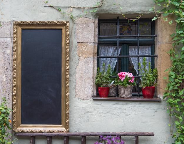 La lavagna nera pronta per essere riempita sul vecchio muro classico in europa Foto Premium