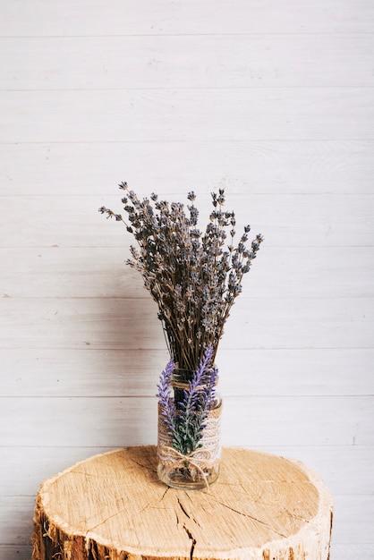 La lavanda fiorisce in bottiglia di vetro sopra il ceppo di albero di legno contro fondo di legno Foto Gratuite