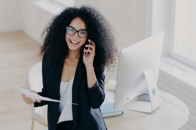 La lavoratrice allegra chiama il partner, tiene documenti cartacei, indossa occhiali da vista e un vestito elegante Foto Premium