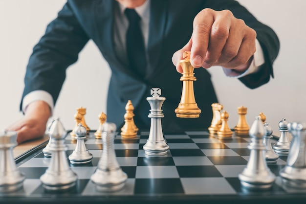 La leadership dell'uomo d'affari che gioca a scacchi e pensa al piano strategico sull'incidente rovescia la squadra opposta e lo sviluppo analizza per il successo dell'azienda Foto Premium