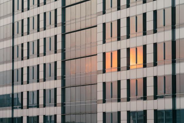 La luce arancione del tramonto si riflette sulla facciata del vetro e del rivestimento di sera. Foto Premium