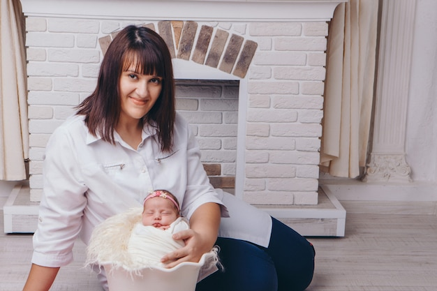 La madre abbraccia il bambino. un neonato, avvolto in una coperta, dorme in un cestino sullo sfondo del camino. concetto di infanzia, assistenza sanitaria, fecondazione in vitro, casa di famiglia Foto Premium