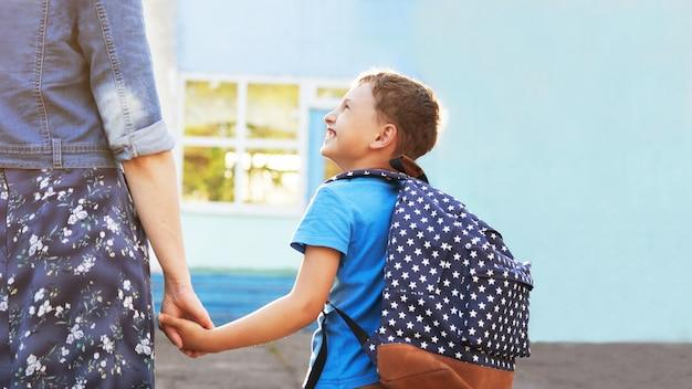 La madre accompagna il bambino a scuola. la mamma incoraggia lo studente che lo accompagna a scuola Foto Premium