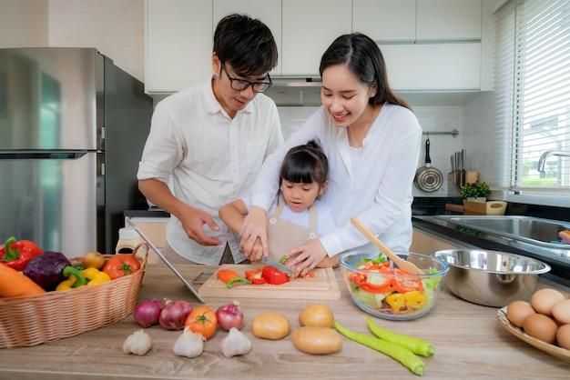 La madre asiatica che insegna a sua figlia ha tagliuzzato l'insalata di verdure. Foto Premium