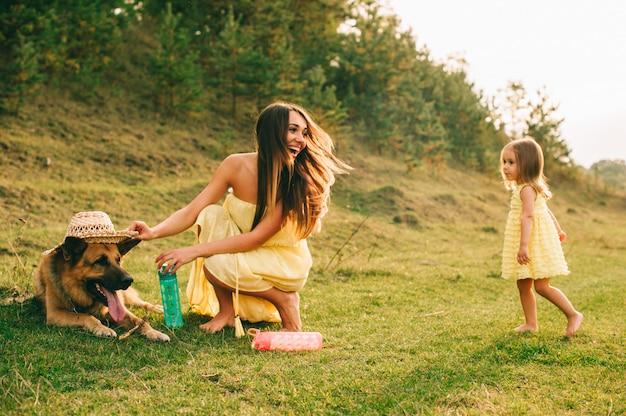 La madre cammina con la sua piccola figlia e il loro cane Foto Premium