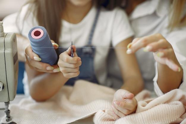 La madre con la piccola figlia cuce i vestiti nella fabbrica Foto Gratuite