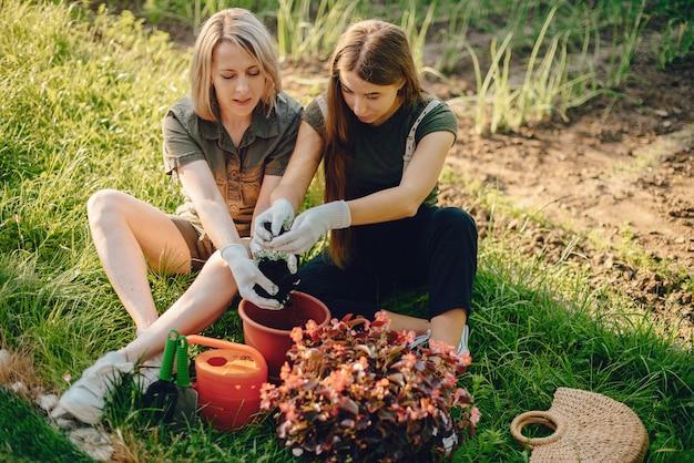 La madre con una figlia lavora in un giardino vicino alla casa Foto Gratuite