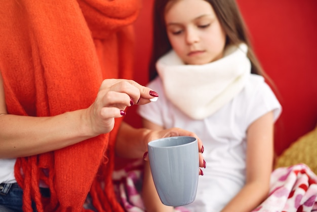 La madre dà a sua figlia malata il tè caldo Foto Gratuite