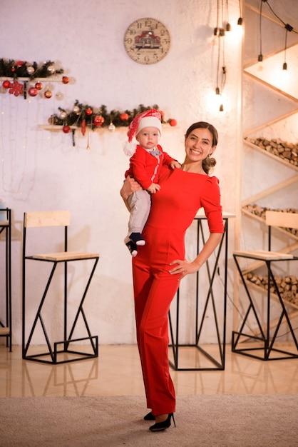 La madre e il bambino con il cappello di babbo natale giocano a casa vicino al camino Foto Premium