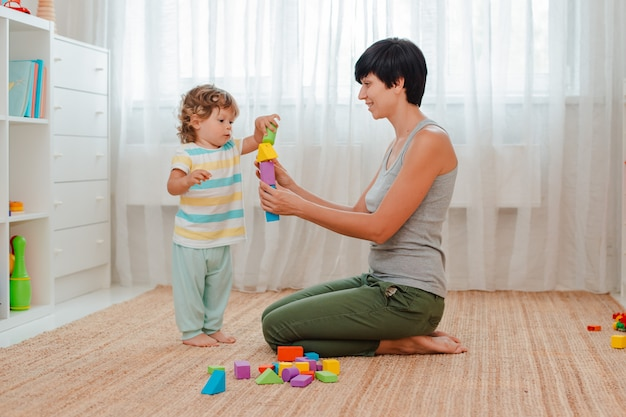 La madre e il bambino giocano sul pavimento nella stanza dei bambini. mamma e bambino stanno costruendo una torre di blocchi colorati. Foto Premium