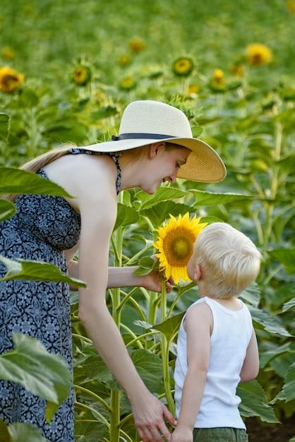 La madre e il figlio stanno in piedi e inalano il profumo del girasole Foto Premium