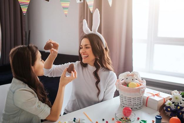 La madre e la figlia allegre preparano per pasqua. tengono le uova di cioccolato e sorridono. decorazione sul tavolo. il modello indossa orecchie di coniglio bianche. Foto Premium