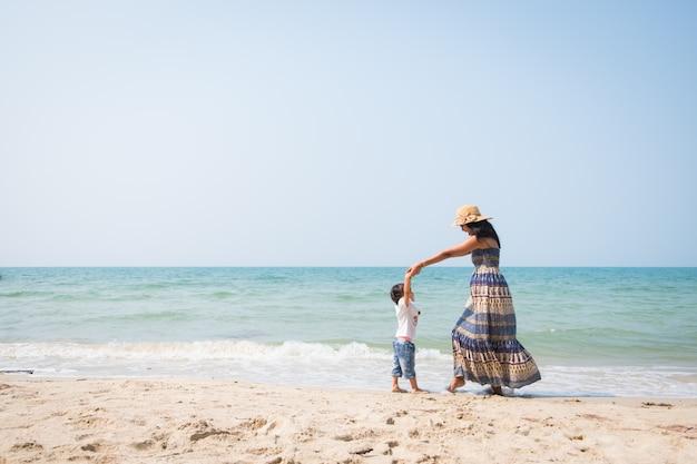 La madre e la figlia asiatiche stanno giocando ballando insieme sulla spiaggia Foto Premium
