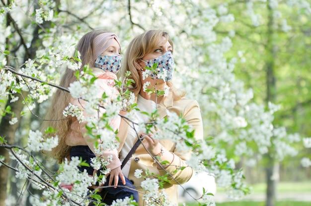 La madre e la figlia con maschere sui fronti sono nella città all'aperto Foto Premium